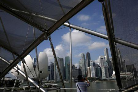 A man takes photos of the skyline of Singapore
