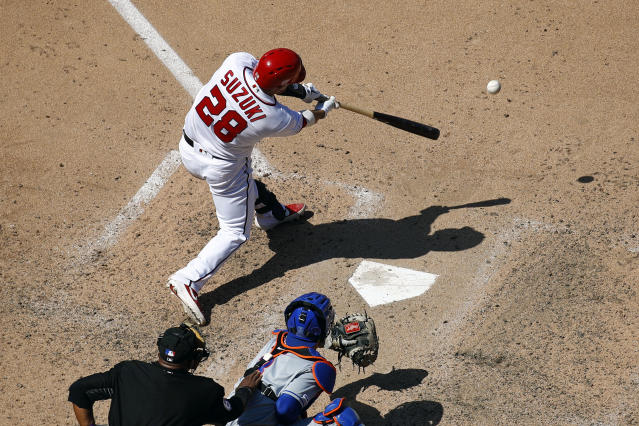 Washington Nationals' Kurt Suzuki singles in front of New York Mets catcher Tomas Nido and umpire Laz Diaz in the seventh inning of a baseball game, Thursday, May 16, 2019, in Washington. Gerardo Parra scored on the play. Washington won 7-6. (AP Photo/Patrick Semansky)