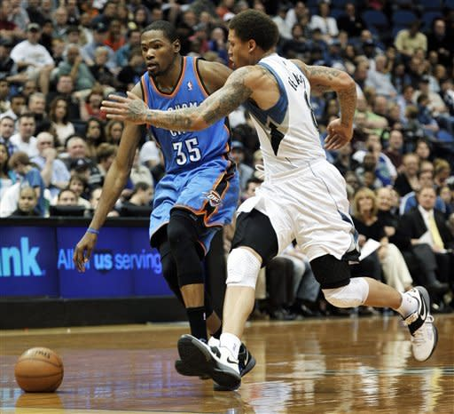 Oklahoma City Thunder's Kevin Durant, left, attempts to drive around Minnesota Timberwolves' Michael Beasley, right, in the second quarter of an NBA basketball game, Saturday, April 14, 2012, in Minneapolis. (AP Photo/Tom Olmscheid)