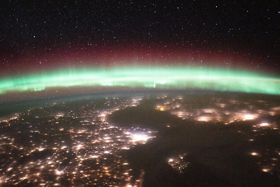 These images, taken from the International Space Station, show Earth's glowing, colorful aurora alongside lights coming from the cities on our planet's surface down below. Aurora is a natural phenomenon in which colorful lights in the sky, which often appear as green, red, yellow or white, are displayed when electrically-charged particles from the sun interact with gases like oxygen or nitrogen in our planet's atmosphere.