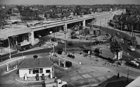 An elevated view looking onto the construction of the Chiswick Flyover and the through road over a 400ft diameter roundabout with a 40ft wide carriageway at the junction of the North Circular Road, Chiswick High Road, the road to Kew Bridge and the Great West Road circa June 1959 in London, United Kingdom. In the centre of the picture is the Esso petrol station and a Police telephone box. (Photo byFox Photos/Hulton Archive/Getty Images). - Credit: Fox Photos/Hulton Archive/Getty Images
