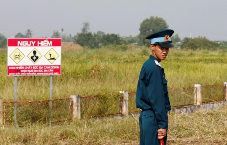 A Vietnamese soldier stands next to a hazardous warning sign by a runway at Bien Hoa air base, a former US air base, on the outskirts of Ho Chi Minh City