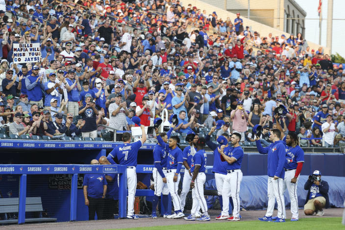 Toronto Blue Jays players raise their hats to fans during the third inning of the team's baseball game against the Boston Red Sox on Wednesday, July 21, 2021, in Buffalo, N.Y. After a road trip, the Blue Jays will once again play home games in Toronto. (AP Photo/Joshua Bessex)