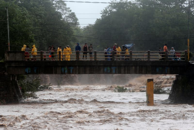 People stand on the bridge that crosses the Masachapa river under the rain caused by Storm Eta in Masachapa
