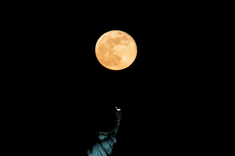 FILE PHOTO: The full moon also known as the Supermoon or Flower Moon rises above the Statue of Liberty as seen from Jersey City