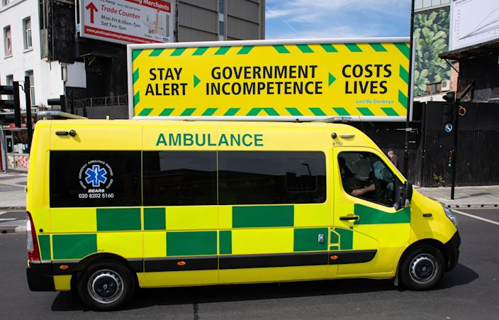 An ambulance passes a billboard by campaign group Led by Donkeys parodying an official government coronavirus message campaign, in central London, after the introduction of measures to bring the country out of lockdown. (Photo by Dominic Lipinski/PA Images via Getty Images)