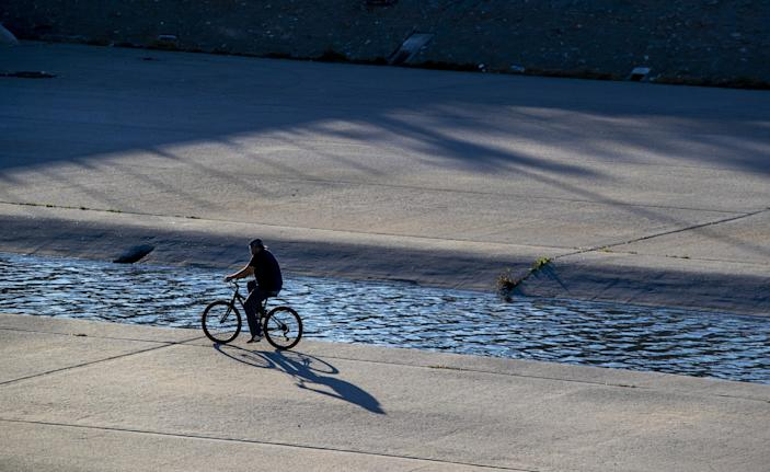 A cyclist rides in the Los Angeles River Sunday, Jan. 10, 2021 in South Gate.