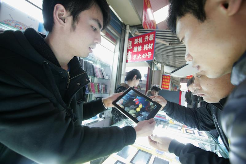 """In this March 4, 2012 photo, a sales clerk shows a customers a counterfeit iPad-like device at a shop in Shanghai, China. Apple's troubles in China over the iPad trademark are not its first, and given its penchant for """"iproducts"""" they are unlikely to be its last. China's importance as a major consumer market is bringing fresh headaches for companies, and even celebrities, seeking to protect and claim brand names. That's on top of the usual problems with piracy and other infringements. (AP Photo)"""