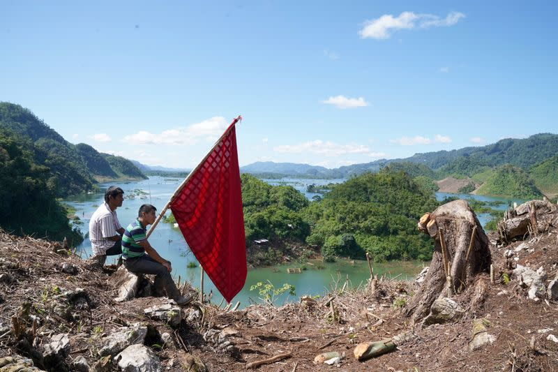 People hold a flag while sitting on the top of a mountain, in the hope of attracting military helicopters delivering aid to villages affected by Hurricanes Eta and Iota, in Alta Verapaz