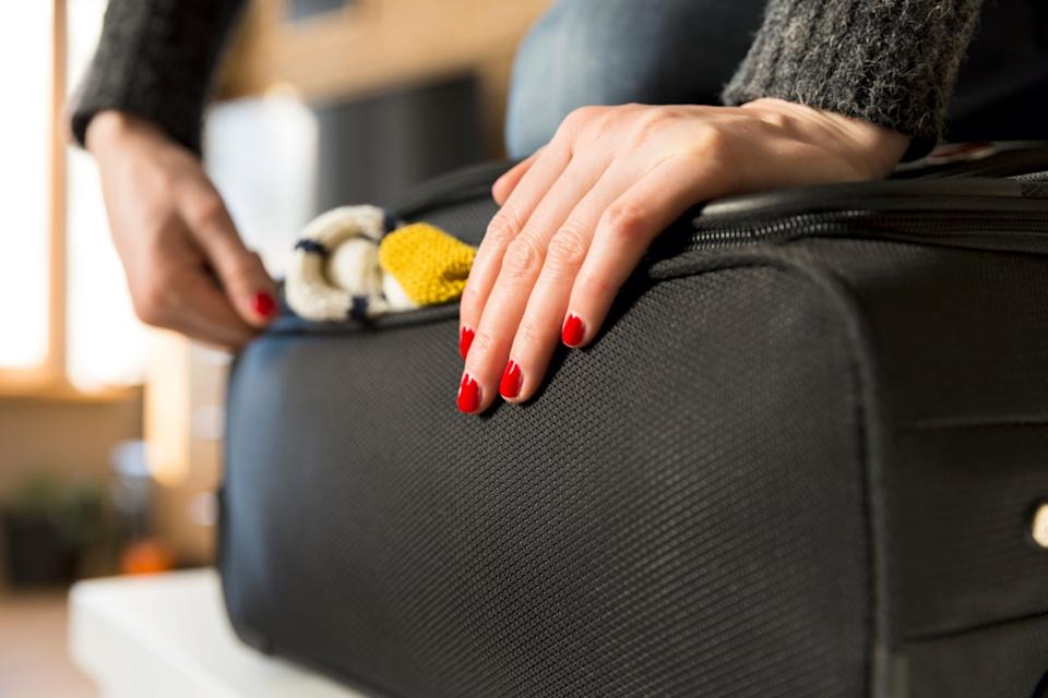 Woman packing for vacation travel trying to close full suitcase
