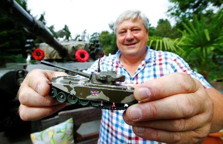 """Gary Blackburn, a 53-year-old tree surgeon from Lincolnshire, Britain, poses with a Centurion toy tank that he received from his father at the age of five years at his British curiosities collection called """"Little Britain"""" in Linz-Kretzhaus, south of Germany's former capital Bonn, Germany, August 24, 2017. REUTERS/Wolfgang Rattay"""