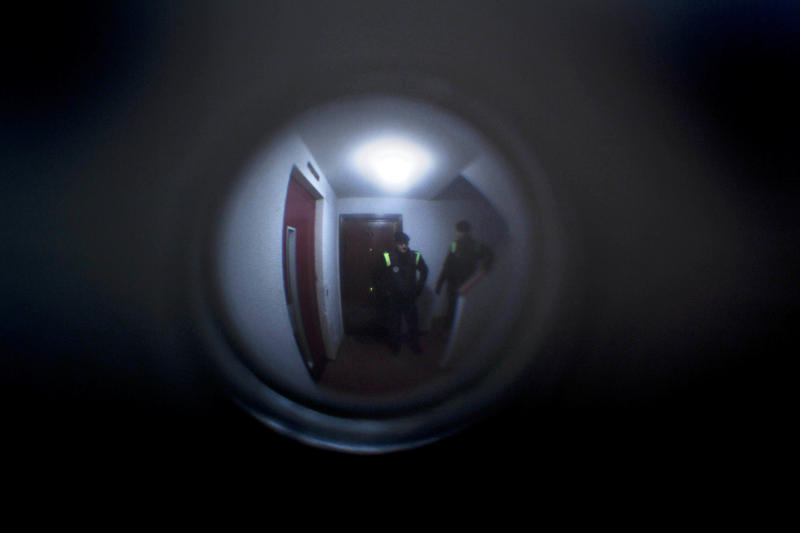 File - In this Nov. 18, 2011 file photo, police officers are seen through peephole of Azucena Paredes's home, an unemployed mother of three children, before her eviction in Madrid. The Spanish government Thursday Nov. 15, 2012 passed a decree curbing evictions of lower income homeowners unable to pay their mortgage, a bid to ease a trend that has seen hundreds of thousands of people lose their homes because of the brutal economic crisis. The urgent measure stops evictions for two years of people whose unemployed benefits have expired or who have incomes of less than euro1,200 ($1,527) a month after tax and whose mortgage represents at least 50 percent total household income. Public attention on the issue intensified greatly in recent weeks after two homeowners facing eviction committed suicide. Spaniards are also angry because while people lose their homes, the government is negotiation billion-dollar bailouts for the same banks who are repossessing the houses. Over the past four years, social groups have begun organizing street protests to try to avoid prevent court officials and police carrying out eviction orders. (AP Photo/Arturo Rodriguez, File)