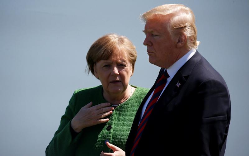 Germany's Chancellor Angela Merkel talks with US President Donald Trump. The President was fiercely critical of German's energy ties with Russia during a recent Nato conference - REUTERS