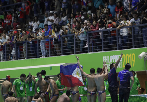 Philippines' water polo team carry the national flag as they acknowledge the cheers from the crowd after their game against Singapore at the 30th South East Asian Games in New Clark City, Tarlac province, northern Philippines on Friday, Nov. 29, 2019. Philippines scored a draw against Singapore 6-6. (AP Photo/Aaron Favila)