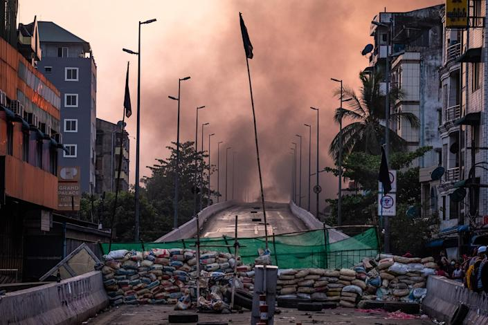 """Smoke rises from tires burning near a barricade erected by protesters to stop government forces from crossing a bridge in Yangon on March 16, 2021.<span class=""""copyright"""">Getty Images</span>"""