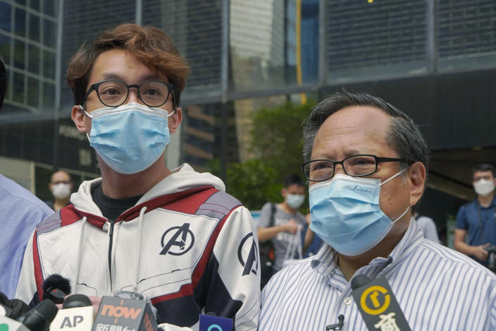 """Various defendants including pro-democracy activists Figo Chan Ho-wun, left, and Albert Ho speak to media outside a court in Hong Kong, Monday, May 17, 2021. Trial starts for Jimmy Lai and nine others, accused of """"incitement to knowingly take part in an unauthorized assembly"""" for a protest march on Oct. 1, 2019. The court has estimated 10 days for this trial. (AP Photo/Kin Cheung)"""