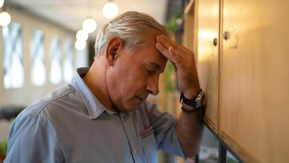 middle age man feeling stressed in office.