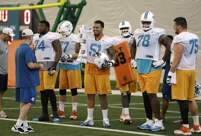 Miami Dolphins center Mike Pouncey (51) stands with guard John Jerry (74), tackle Bryant McKinnie (78) and guard Nate Garner (75) during NFL football practice, Wednesday, Nov. 6, 2013, in Davie, Fla. At left is offensive line coach Jim Turner. (AP Photo/Lynne Sladky)