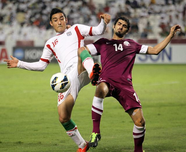 FILE - In this June 4, 2013, file photo, Qatar's Ibrahim Al-Ghanim , right, battles against Iran's Reza Ghoochannejhad during their 2014 World Cup Asian zone qualifying soccer match at the Al-Sadd stadium in Doha. (AP Photo/Osama Faisal,File)