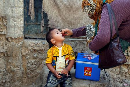 FILE PHOTO: A boy receives polio vaccine drops, during an anti-polio campaign, in a low-income neighbourhood in Karachi, Pakistan April 9, 2018. REUTERS/Akhtar Soomro/File Photo