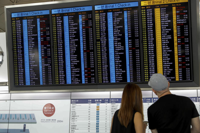 Travellers check on information of their flight at the airport in Hong Kong, Wednesday, Aug. 14, 2019. Flight operations resumed at the airport Wednesday morning after two days of disruptions marked by outbursts of violence highlighting the hardening positions of pro-democracy protesters and the authorities in the Chinese city that's a major international travel hub. (AP Photo/Vincent Thian)