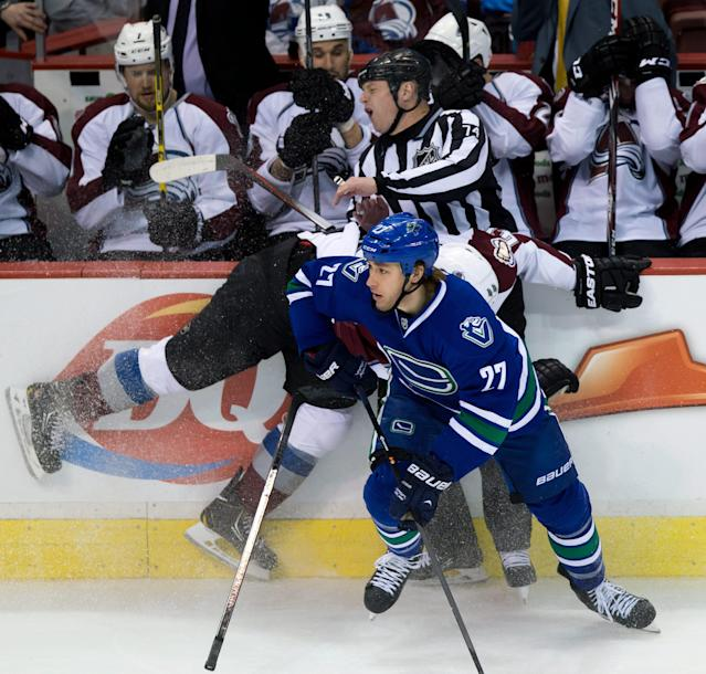 Colorado Avalanche's Ryan Wilson, middle, collides with linesman Lonnie Cameron while trying to check Vancouver Canucks' Shawn Matthias during the third period of an NHL hockey game Thursday, April 10, 2014, in Vancouver, British Columbia. (AP Photo/The Canadian Press, Darryl Dyck)