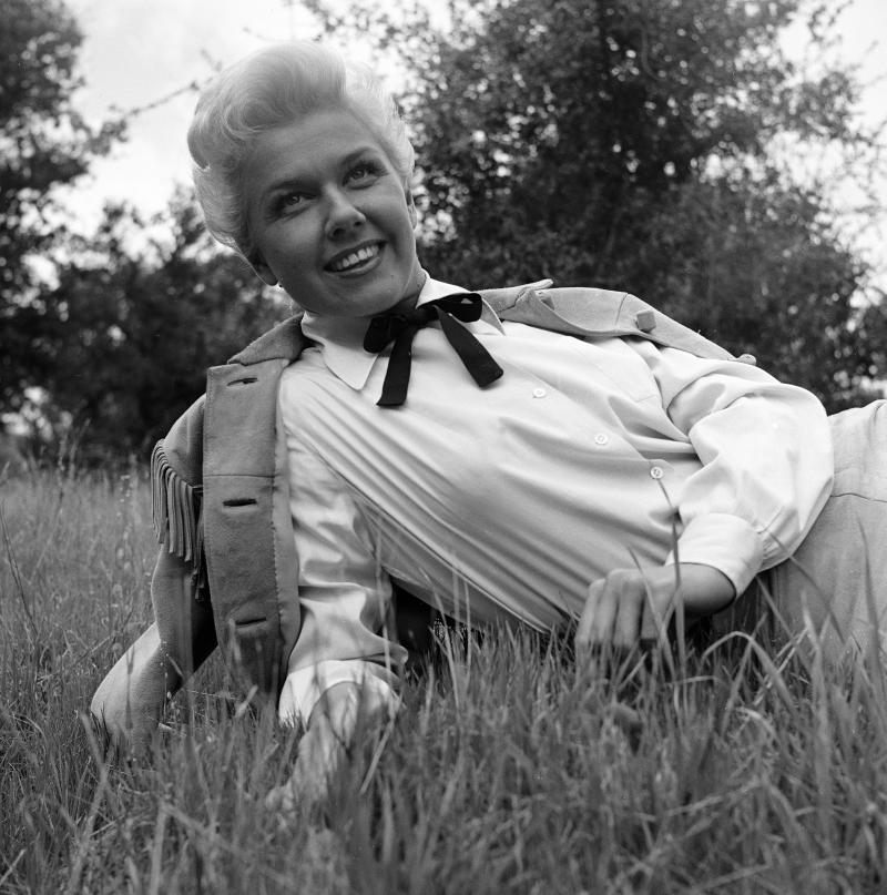American actress and singer Doris Day lies on the grass, propped up on one elbow, in a white blouse with a buckskin coat over her shoulders, a photo shoot to publicize the musical film 'Calamity Jane' directed by David Butler, 1953. (Photo by Ed Clark/The LIFE Picture Collection via Getty Images)