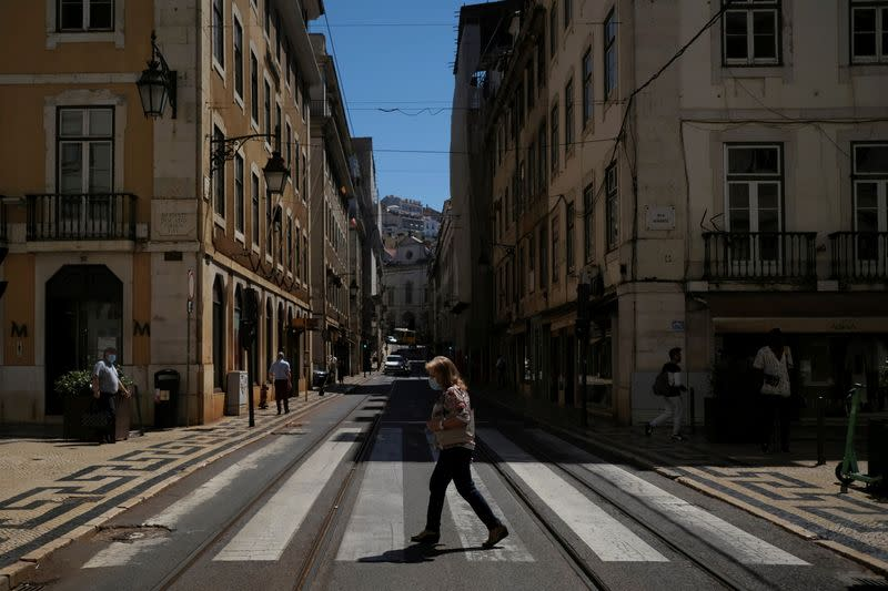 FILE PHOTO: A person wearing a protective mask walks in Lisbon downtown amid the coronavirus disease (COVID-19) pandemic, in Lisbon