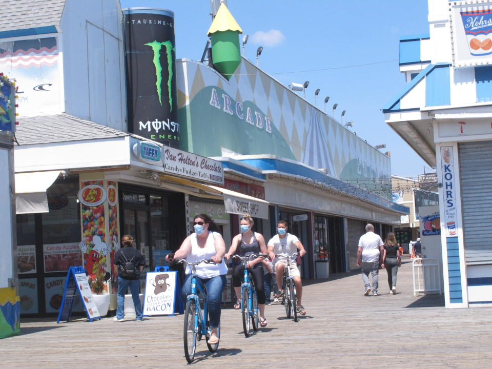Bicyclists ride on the boardwalk in Seaside Heights, N.J. on May 15, 2020, the on the first day it opened during the coronavirus outbreak. It and another popular Jersey Shore beach, Point Pleasant Beach, were among those allowing people back onto the sand with some restrictions to try to slow the spread of the virus. (AP Photo/Wayne Parry)