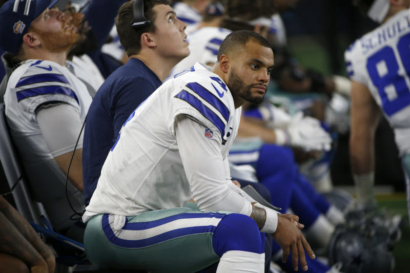 Dallas Cowboys quarterback Dak Prescott (4) and offensive coordinator Kellen Moore, rear, sit on the bench late in the second half of an NFL football game against the Buffalo Bills in Arlington, Texas, Thursday, Nov. 28, 2019. (AP Photo/Ron Jenkins)