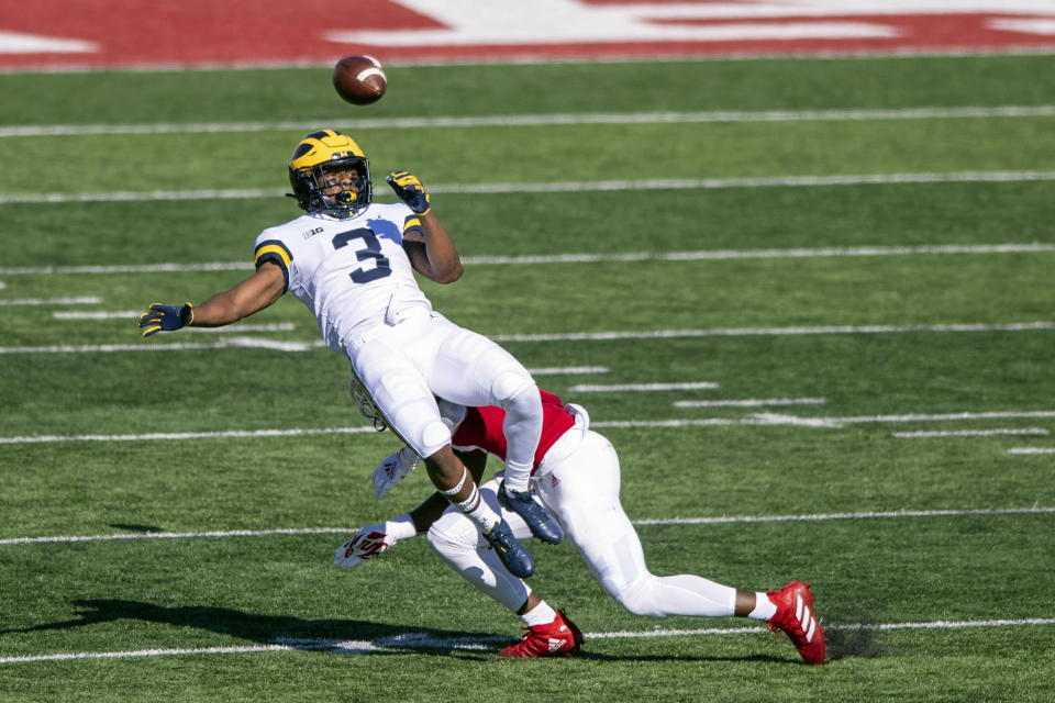 Michigan wide receiver A.J. Henning (3) loses control of the ball as he's hit by Indiana defensive back Devon Matthews (1) during the first half of an NCAA college football game Saturday, Nov. 7, 2020, in Bloomington, Ind. (AP Photo/Doug McSchooler)