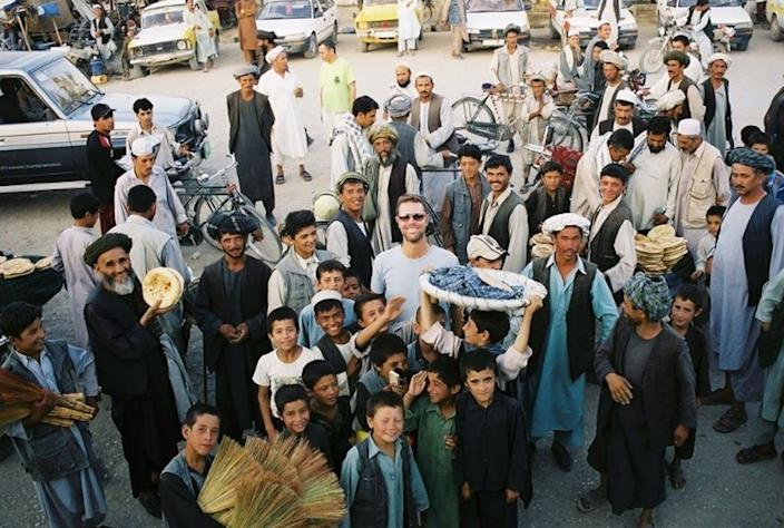 A crowd of Afghans smile around a guest