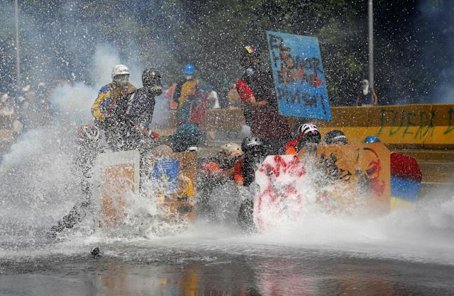 "<p>Opposition supporters clash with riot security forces while rallying against President Nicolas Maduro in Caracas, Venezuela, May 18, 2017. The sign on top right reads ""Honor is my badge."" (Marco Bello/Reuters) </p>"