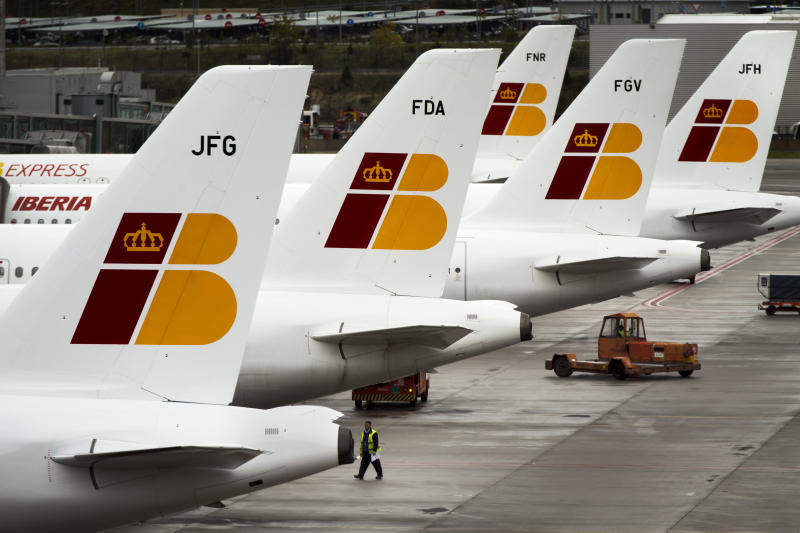 "A man walks besides Iberia jets in a parking zone at Barajas international airport in Madrid, Friday, Nov. 9, 2012. International Airlines Group on Friday warned that its Spanish carrier Iberia was ""in a fight for survival"" and unveiled a restructuring plan to cut 4,500 jobs as it reported a drop in third-quarter profit. (AP Photo/Daniel Ochoa de Olza)"