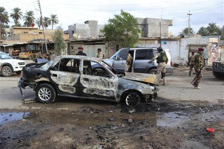 Iraqi security forces inspect the site of car bomb attack in Buhriz