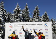 Bobsleigh pilot Kaillie Humphries of the United States, center, celebrates on the podium after taking first place in the women's monobob race at the Bobsleigh and Skeleton World Championships in Altenberg, Germany, Sunday, Feb.14, 2021. At left is second place Germany's Stephanie Schneider and at right is third place Germany's Laura Nolte. (AP Photo/Matthias Schrader)