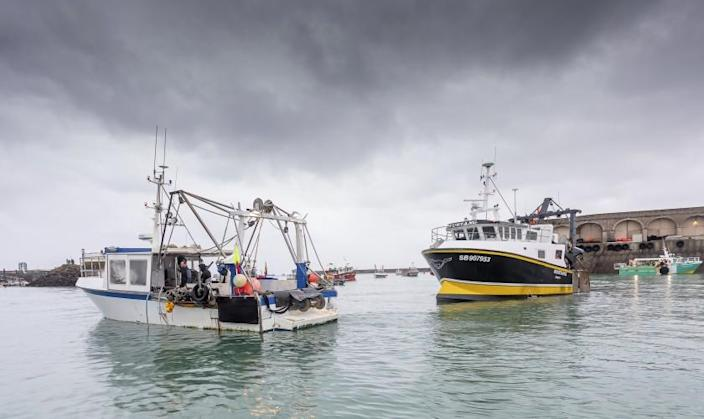 French fishing vessels block the port of St Helier in Jersey, Thursday, May 6, 2021. French fishermen angry over loss of access to waters off their coast have gathered their boats in protest off the English Channel island of Jersey. The head of a grouping of Normandy fishermen said about 50 boats from French ports joined the protest Thursday morning and gathered their fleet off the Jersey port of St. Helier. (Gary Grimshaw/Balliwick Express via AP)