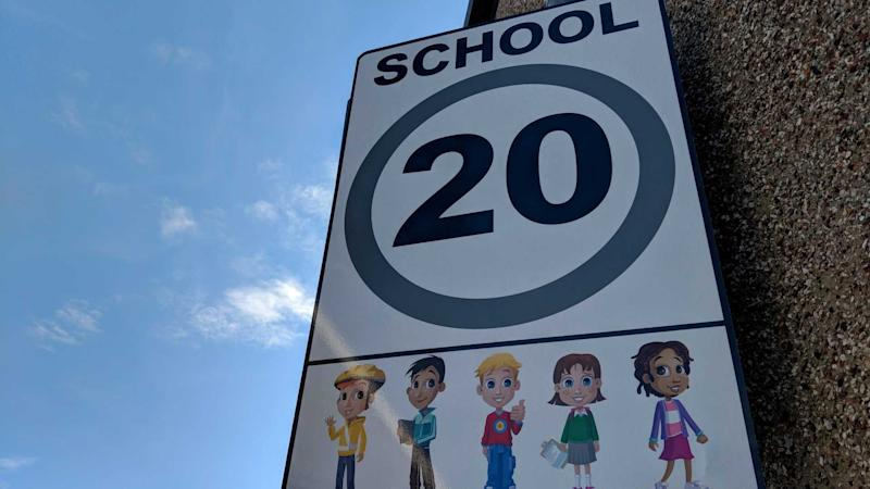 20 mph speed limit sign with illustration of ethnically diverse school children