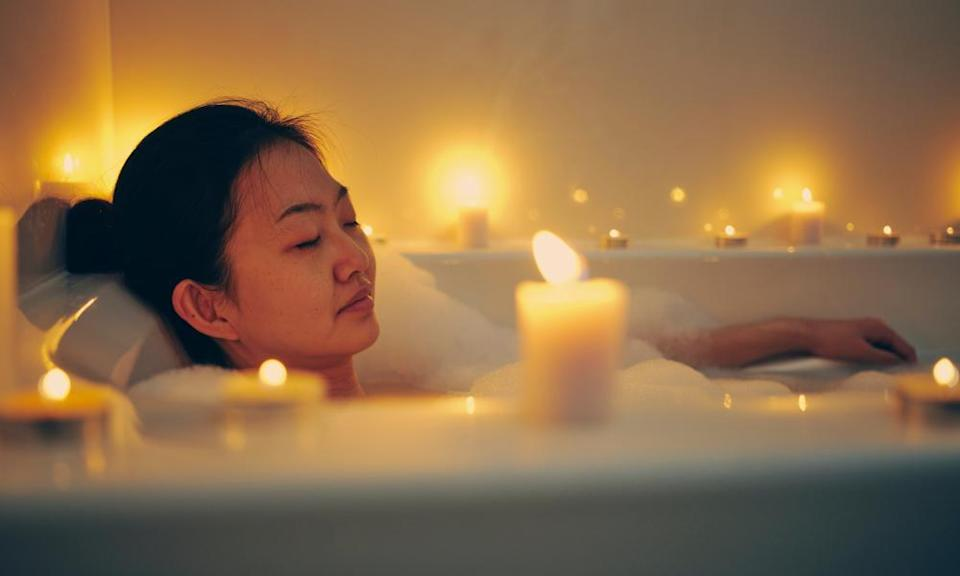 A woman relaxes in a candlelit bath