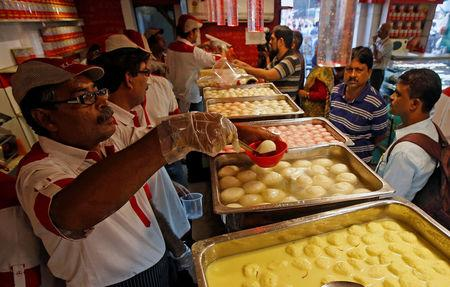 Customers purchase 'Rosogolla', popularly known as the king of Indian sweets, inside a sweet shop in Kolkata, India, November 14, 2017. REUTERS/Rupak De Chowdhuri