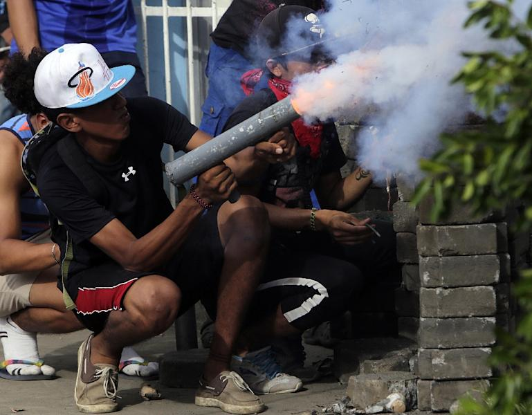 An anti-government demonstrator fires a homemade mortar during clashes with riot police at a barricade in the town of Masaya (AFP Photo/INTI OCON)