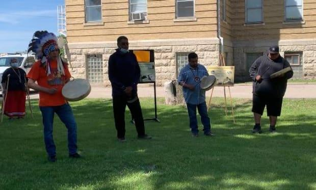 Long Plain First Nation Chief Dennis Meeches, left, sings an honour song on the grounds of the former Portage la Prairie Indian Residential School at a ceremony in honour of the children whose remains were recently discovered in unmarked graves in Kamloops, B.C.