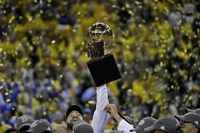 <p>Golden State Warriors center JaVale McGee holds up the Larry O'Brien NBA Championship Trophy after Game 5 of basketball's NBA Finals between the Warriors and the Cleveland Cavaliers in Oakland, Calif., Monday, June 12, 2017. The Warriors won 129-120 to win the NBA championship. (AP Photo/Marcio Jose Sanchez) </p>