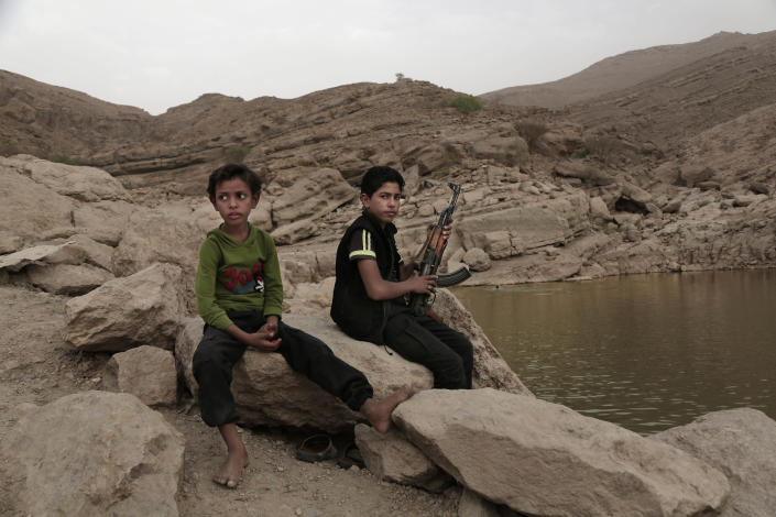 FILE - In this July 30, 2018, file photo, a 17-year-old boy holds his weapon at the dam in Marib, Yemen. The battle for the ancient desert city has become key to understanding wider tensions now inflaming the Middle East and the challenges facing any efforts by President Joe Biden's administration to shift U.S. troops out of the region. (AP Photo/Nariman El-Mofty, File)