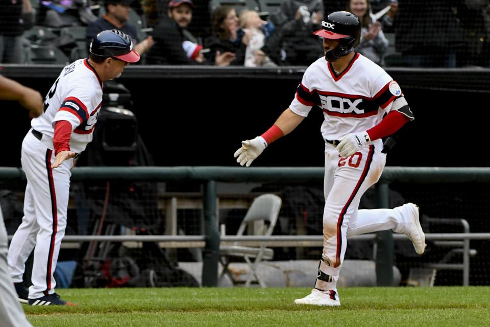 Chicago White Sox's Danny Mendick (20) is congratulated by third base coach Nick Capra, left, after hitting a home run off Los Angeles Angels' Jaime Barria during the fifth inning of a baseball game Sunday, Sept. 8, 2019, in Chicago. (AP Photo/Matt Marton)