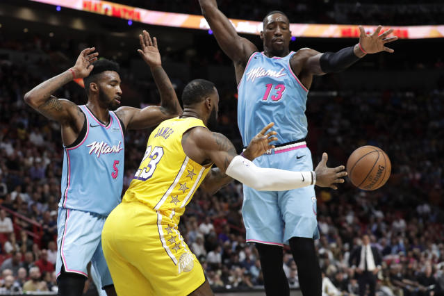 Los Angeles Lakers forward LeBron James (23) passes as Miami Heat forward Derrick Jones Jr. (5) and center Bam Adebayo (13) defend during the first half of an NBA basketball game, Friday, Dec. 13, 2019, in Miami. (AP Photo/Lynne Sladky)