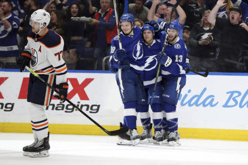 Tampa Bay Lightning's Yanni Gourde, center is congratulated on his goal by teammates Mikhail Sergachev (98), of Russia, and Cedric Paquette (13), as Edmonton Oilers' Oscar Klefbom, of Sweden, skated away during the second period of an NHL hockey game Thursday, Feb. 13, 2020, in Tampa, Fla. (AP Photo/Mike Carlson)