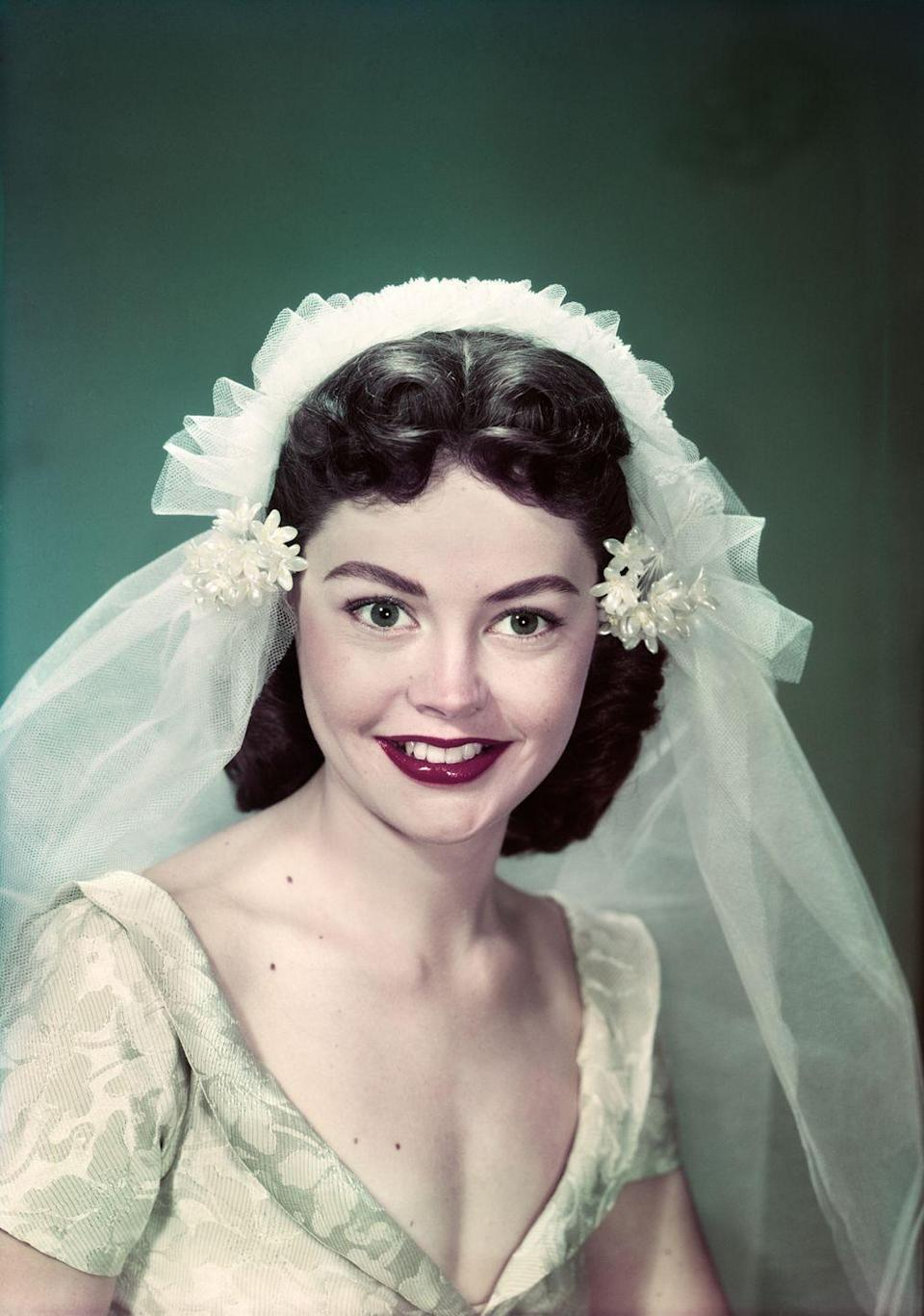 <p>Necklines plunged during 1949, and wedding gowns were no exception. Shoulder-length, curled hair was also in style, and veils became shorter and simpler. </p>