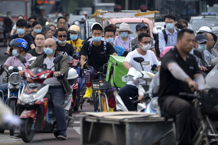 """People riding bicycles and scooters wait to cross an intersection during rush hour in Beijing, Friday, July 2, 2021. A small but visible handful of urban Chinese are rattling the ruling Communist Party by choosing to """"lie flat,"""" or reject high-status careers, long work hours and expensive cities for a """"low-desire life."""" That clashes with party ambitions to make China a wealthier consumer society. (AP Photo/Mark Schiefelbein)"""