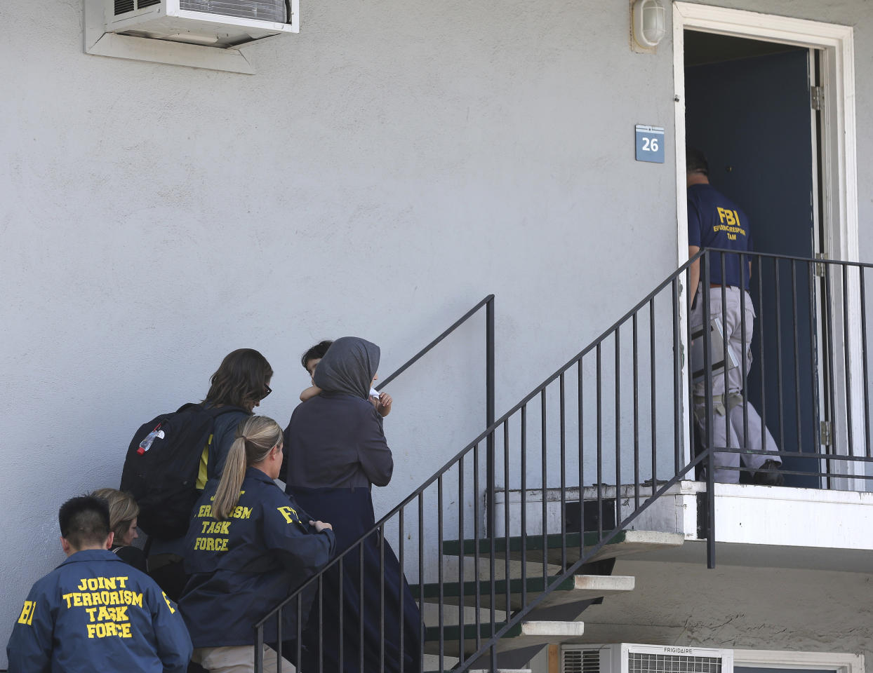 A woman carrying a child is escorted by authorities to an apartment following the arrest of a 45-year-old Iraqi refugee, Omar Ameen, Wednesday, Aug. 15, 2018, in Sacramento, Calif. Ameen was arrested on a warrant alleging that he killed an Iraqi policeman in 2014 while serving with the Islamic State terror organization. (AP Photo/Rich Pedroncelli)